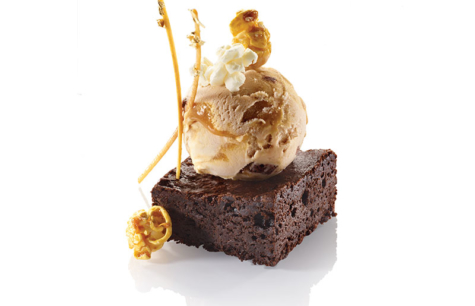 BROWNIE CHUNKS A CARAMEL VANILLA ICE CREAM, DARK CHOCOLATE BROWNIE, POPCORN, CARAMEL AND G...