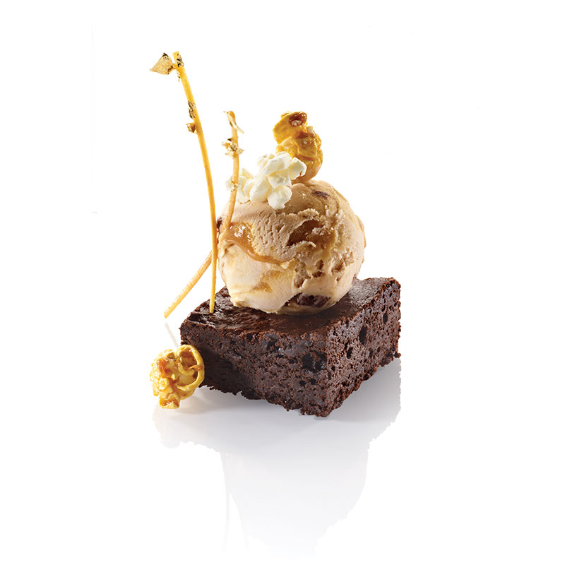 BROWNIE CHUNKS A CARAMEL VANILLA ICE CREAM, DARK CHOCOLATE BROWNIE, POPCORN, CARAMEL AND GOLDEN SHORT CUT PASTRY STICKS